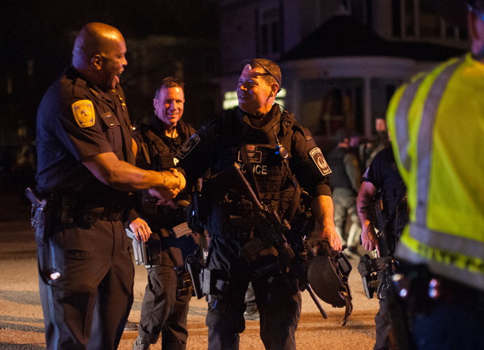 Police officers and SWAT team members greet each other after a police assault on a house on Franklin Street in Watertown, Massachusetts April 19, 2013.(Reuters / John Taggart)