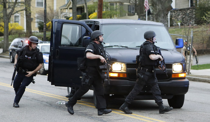 Police SWAT team members run towards the scene of gunfire as police assault a house on Franklin Street during the search for Dzhokhar Tsarnaev, the surviving suspect in the Boston Marathon bombings, in Watertown, Massachusetts April 19, 2013. (Reuters/Jim Bourg)