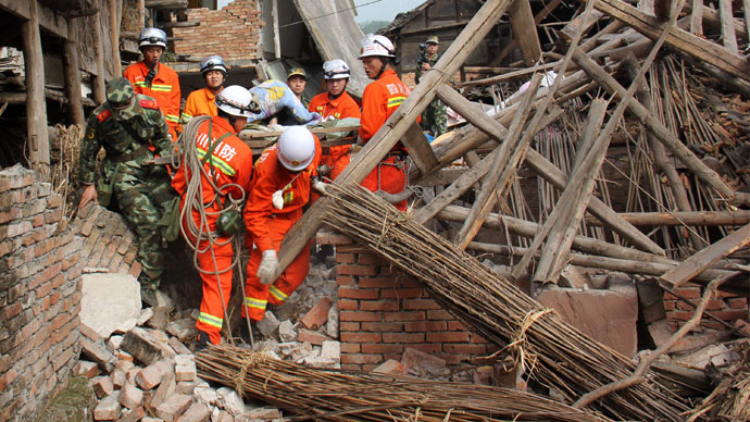 Rescuers carry a paralysed elderly man from his damaged house in Qingren township in seriously damaged Lushan county after a shallow earthquake at magnitude 7.0 hit the city of Ya'an, in southwest China's Sichuan province on April 20, 2013.(AFP Photo / China OUT)