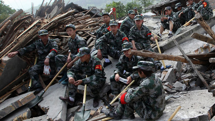 Rescuers sit on ruins of a house in Longmen township, an area very close to the epicenter of a shallow earthquake at magnitude 7.0 that hit the city of Ya'an, southwest China's Sichuan province on April 20, 2013.(AFP Photo / China OUT)