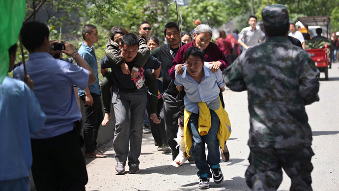 Men carry injured people to an ambulance at Longmen Village, Lushan county, Ya'an, Sichuan province, April 20, 2013.(Reuters / Stringer)