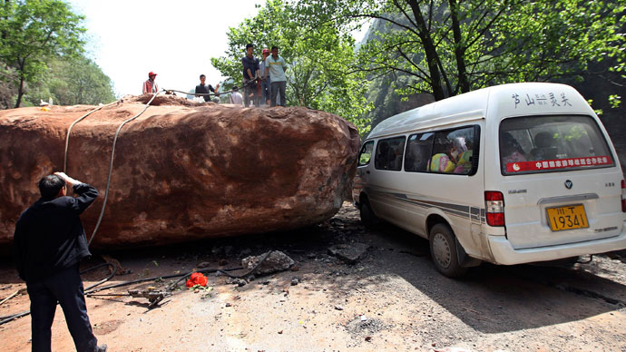 People stand near a van on a road blocked by a large rock after a strong 6.6 magnitude earthquake, at Longmen village, Lushan county, Ya'an, Sichuan province April 20, 2013.(Reuters / Stringer)