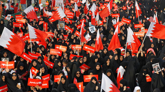 "Protesters holding banners that read ""I Love Bahrain"" participate with Bahraini flags during an anti-government rally organised by main opposition group Al Wefaq in Budaiya, west of Manama April 19, 2013.(Reuters / Hamad I Mohammed)"