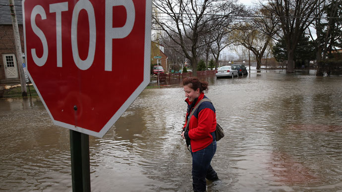 A woman walks down a flooded sidewalk on April 19, 2013 in Des Plaines, Illinois.(AFP Photo / Scott Olson)