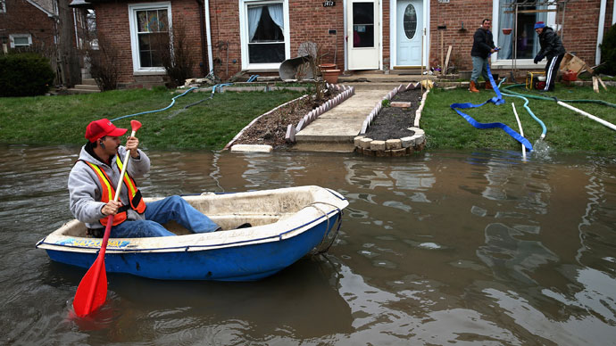 Octavio Castillo paddles a boat down a flooded street to reach the home of his cousin on April 19, 2013 in Des Plaines, Illinois.(AFP Photo / Scott Olson)
