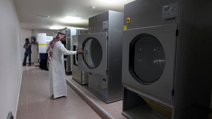 "A local media representative looks at a washing machine during a tour of a new centre for the rehabilitation of suspected ""terrorists"" and potential al-Qaeda recruits in Riyadh on April 9, 2013.(AFP Photo / STR)"