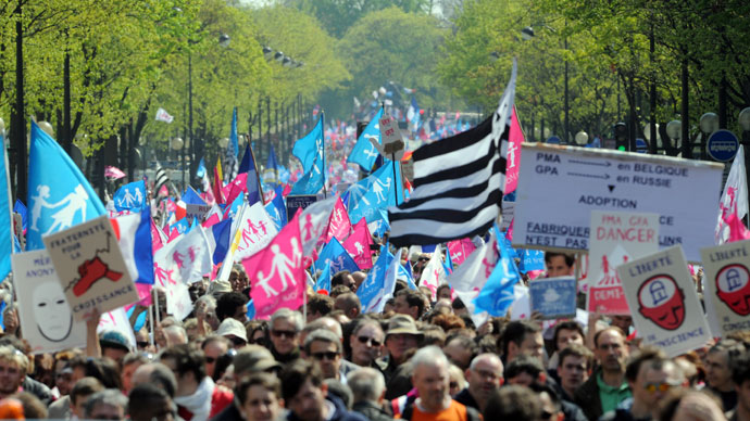 """Thousands of opponents of a gay marriage wave flags as they walk during a demonstration of the anti-gay marriage movement """"La Manif Pour Tous"""" (Demonstration for all!) on April 21, 2013 in Paris.(AFP Photo / Pierre Andryieu)"""