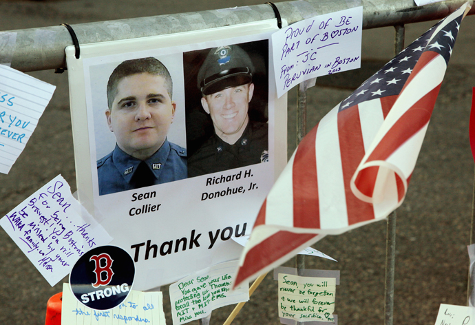 A tribute to MIT police officer Sean Collier (L), killed by the Boston marathon bombing suspects and MBTA police officer Richard Donahue, Jr. (R), shot and injured in a shoot out with the suspects, is seen at a memorial to the victims of the Boston Marathon bombings near the scene of the blasts on Boylston Street in Boston, Massachusetts, April 21, 2013. ( Reuters / Jim Bourg)