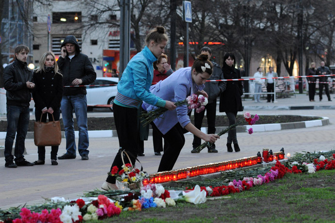 City residents lay flowers to the site of a shooting spree on Narodny Boulevard in Belgorod which claimed six lives. (RIA Novosti/Mikhail Malykhin)