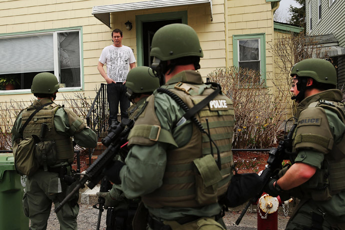 Members of a police SWAT team talk to a man while conducting a door-to-door search for 19-year-old Boston Marathon bombing suspect Dzhokhar A. Tsarnaev on April 19, 2013 in Watertown, Massachusetts. (Spencer Platt/Getty Images/AFP)