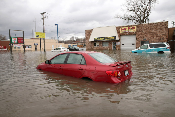 A car is stranded in the middle of a downtown street after being overcome by floodwater April 19, 2013 in Des Plaines, Illinois. (Scott Olson/Getty Images/AFP)