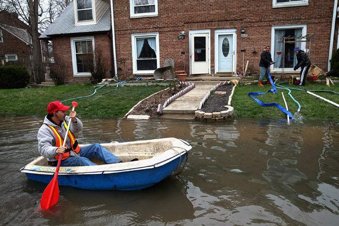 Octavio Castillo paddles a boat down a flooded street to reach the home of his cousin on April 19, 2013 in Des Plaines, Illinois. (Scott Olson/Getty Images/AFP)