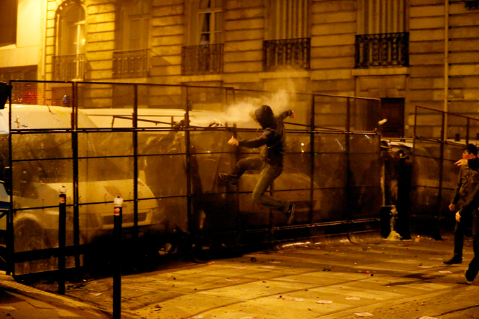 An opponent to the same sex marriage leaps against police barriers during a demonstration near the National Assembly, on April 23, 2013 in Paris (AFP Photo / Kenzo Tribouillard)