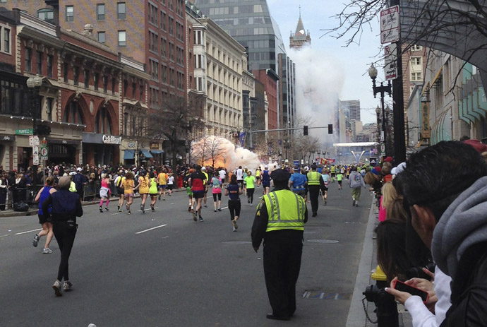 Runners continue to run towards the finish line of the Boston Marathon as an explosion erupts near the finish line of the race in this photo exclusively licensed to Reuters by photographer Dan Lampariello after he took the photo in Boston, Massachusetts, April 15, 2013. (Reutrers/Dan Lampariello)