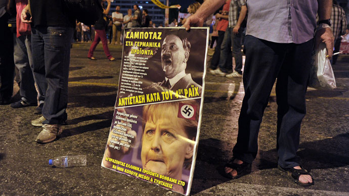 An anti-austerity protester holds a placard against the German Chancellor Angela Merkel during a demonstration in Athens.(AFP Photo / Louisa Gouliamaki)