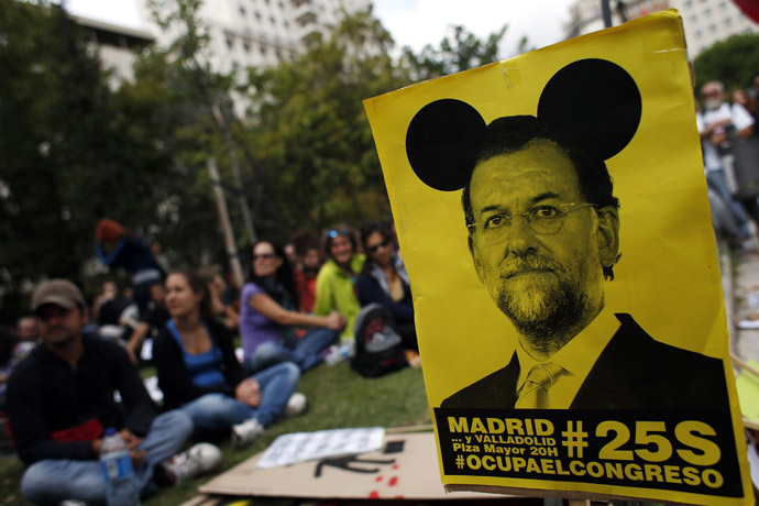 Demonstrators sit next to a sign with an image of Spanish Prime Minister Mariano Rajoy as they wait for the start of an assembly before an anti-austerity demonstration in Madrid September 25, 2012. (Reuters)