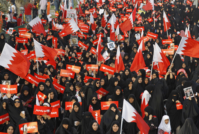 "Protesters holding banners that read ""I Love Bahrain"" participate with Bahraini flags during an anti-government rally organised by main opposition group Al Wefaq in Budaiya, west of Manama April 19, 2013. (Reuters/Hamad I Mohammed)"