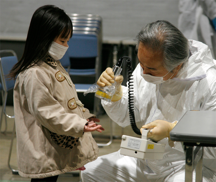 A little girl holds out her hands for a radiation scan at a screening center in Koriyama in Fukushima prefecture (AFP Photo)