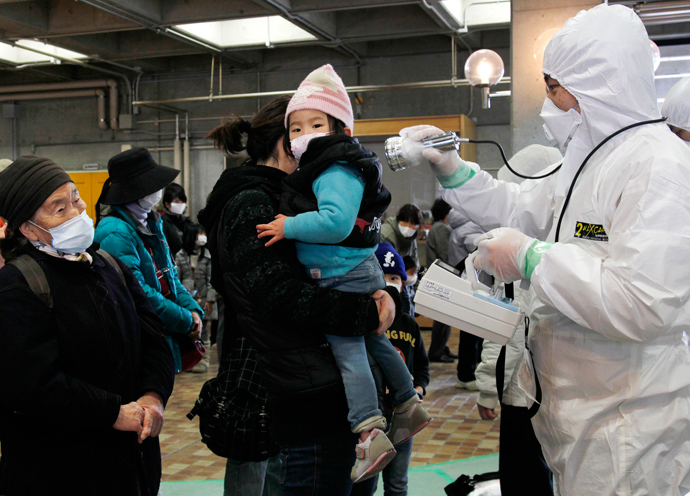 An official in a full radiation protection suit scans an evacuated mother and child with a geiger counter to check radiation levels in Koriyama city in Fukushima prefecture, about 60km west from the crisis-hit Tokyo Electric Power Co (TEPCO) Fukushima Nuclear plant (AFP Photo / Ken Shimizu)