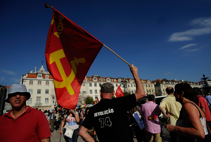 "A demonstrator waves a comunist flag and wears a T-shirt reading ""revolution 74"" in Lisbon's main Rossio Square during the celebration of the1974 Revolution anniversary on April 25, 2013 (AFP Photo / Francisco Leong)"