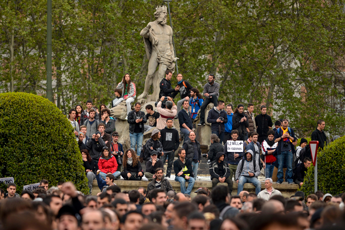 People gather on the Neptune fountain in front of fences blocking the street leading to the Spain's parliament (Las Cortes) during an anti-government demonstration in Madrid on April 25, 2013 (AFP Photo / Pedro Armestre)