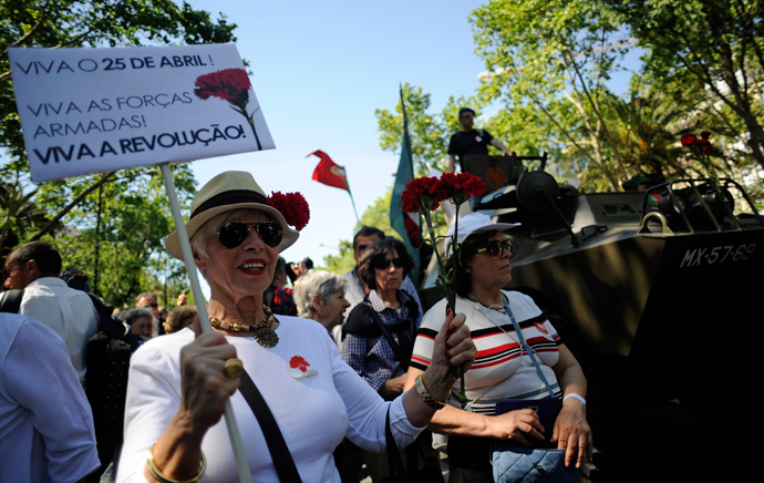 A woman holds red carnations and a board praising military forces and revoltion as she marches in Lisbon's main Liberdade Avenue during the celebration of the1974 Revolution anniversary on April 25, 2013 (AFP Photo / Francisco Leong)