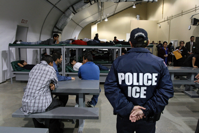 An Immigration and Customs Enforcement (ICE) officer guards a group of 116 Salvadorean immigrants waiting to be deported at the Willacy Detention facility in Raymondville, Texas (AFP Photo / Jose Cabezas)