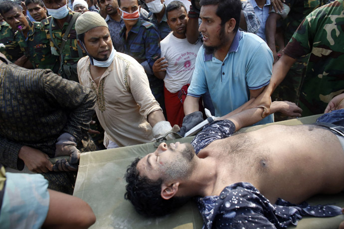 Rescue workers carry a garment worker alive from the rubble of the collapsed Rana Plaza building, in Savar, 30 km (19 miles) outside Dhaka April 26, 2013. (Reuters/Andrew Biraj)