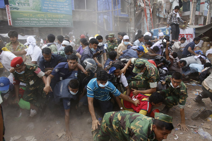 Rescue workers, army personnel, police and members of media run after they heard someone shouting that a building next to Rana Plaza is collapsing during a rescue operation in Savar, 30 km (19 miles) outside Dhaka April 26, 2013. (Reuters/Andrew Biraj)