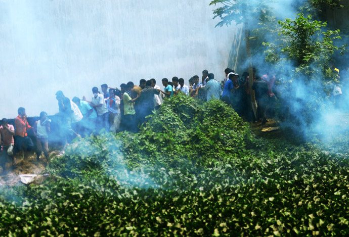 Bangladeshi police fire tear gas after relatives of the missing and dead burst into angry protests at the disaster site of an eight-storey building that collapsed 48 hours earlier in Savar, on the outskirts of Dhaka, on April 26, 2013. (AFP Photo/Munir Uz Zaman)