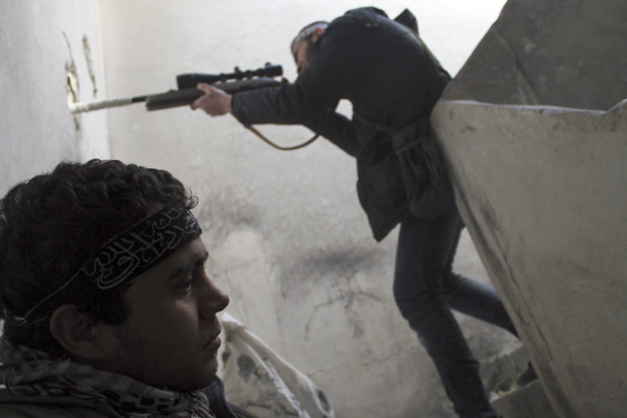 A member of the Free Syrian Army points his weapon through a hole in a wall as he takes up a defence position near Aleppo International Airport February 15, 2013. (Reuters/Saad Abobrahim)