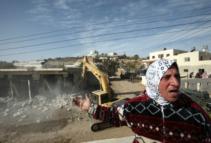 A Palestinian woman from the Jaber family shouts as Israeli bulldozers demolished a series of shops built without a permit in the vicinity of the Israeli settlement of Kiryat Arbaa. (AFP Photo / Hazem Bader)