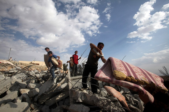 Palestinians search for their belongings in the rubble of their houses, which were demolished by Israeli bulldozers as they were built illegally without a permit in the southern area of Yatta village, south of the West Bank town of Hebron, on November 6, 2012. (AFP Photo / Hazem Bader)