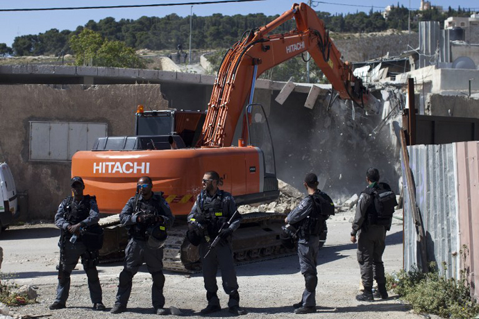 Israeli security officers stand guard as a bulldozer hired by the Jerusalem municipality destroys a Palestinian house in the Israeli annexed East Jerusalem neighborhood of al-Tur on April 24, 2013. (AFP Photo / Ahmad Gharabli)