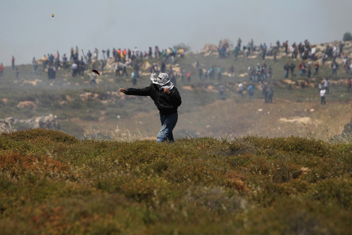 A Palestinian demonstrator uses a sling shot to throw rocks towards Israeli security forces during clashes following a march against construction on their land by members of the Jewish settlement of Ofra on April 26, 2013. (AFP Photo / Abbas Momani)