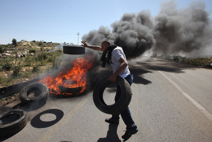 A Palestinian demonstrator burns tyres during during clashes with Israeli soldiers following a march against construction on their land by members of the nearby Jewish settlement of Ofra on April 26, 2013. (AFP Photo / Abbas Momani)