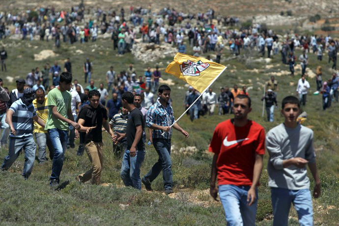 A Palestinian demonstrator from the West Bank village of Deir Jarir waves the Fatah movement flag as he marches with fellow protestors against construction on their land by members of the nearby Jewish settlement of Ofra on April 26, 2013. (AFP Photo / Abbas Momani)