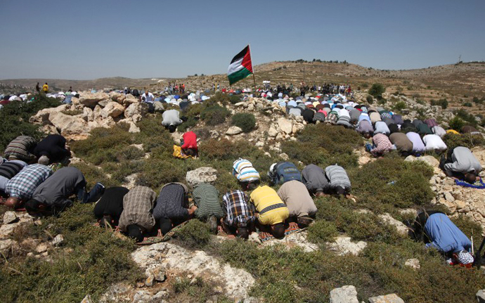 A Palestinian demonstrator from the West Bank village of Deir Jarir, waves his national flag as as others pray prior to clashes with Israeli soldiers on April 26, 2013. (AFP Photo / Abbas Momani)