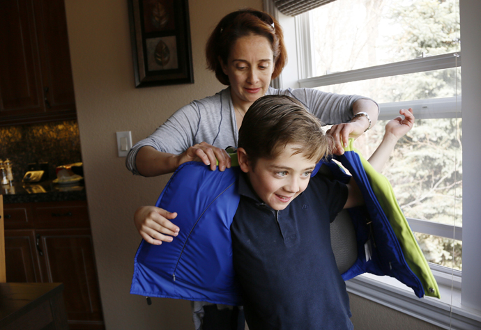 Sheirn Adi helps her son Bilal, 8, put on a bullet proof vest/backpack combination called the V-Bag sold by Elite Sterling Security LLC (ESS) in Aurora, Colorado March 19, 2013. (Reuters / Rick Wilking)