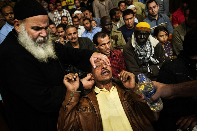 An Egyptian man reacts after being sprayed with holy water by Coptic priest Abraam Fahmi (left) during a function on April 25, 2013 at the St Samaans (Simon) Church. (AFP Photo / Gianluigi Guercia)
