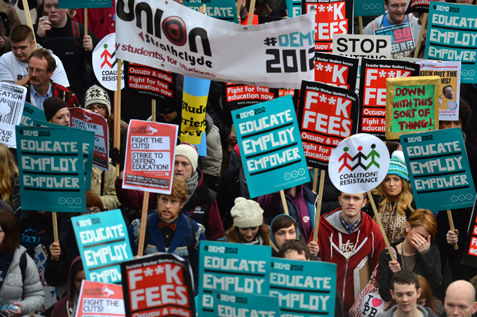 Demonstrators hold placards as they gather before the start of a student rally in central London against sharp rises in university tuition fees, funding cuts and high youth unemployment (AFP Photo / Ben Stansall)