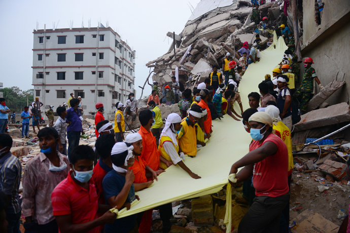Bangladeshi rescue worker holds a length of textile as a slide to move dead victims recovered 60 hours later, from the rubble of a collapsed eight-storey building in Savar, on the outskirts of Dhaka, on April 26, 2013 (AFP Photo / Muniz Uz Zaman)