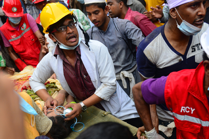 Bangladeshi rescue worker assists a survivor after she was recovered, 60 hours later, from the rubble of a collapsed eight-storey building in Savar, on the outskirts of Dhaka, on April 26, 2013 (AFP Photo / Muniz Uz Zaman)