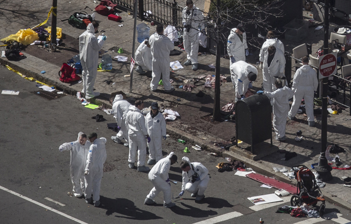 Investigators survey the site of a bomb blast on Boylston Street a day after two explosions hit the Boston Marathon in Boston, Massachusetts April 16, 2013. (Reuters / Adrees Latif)