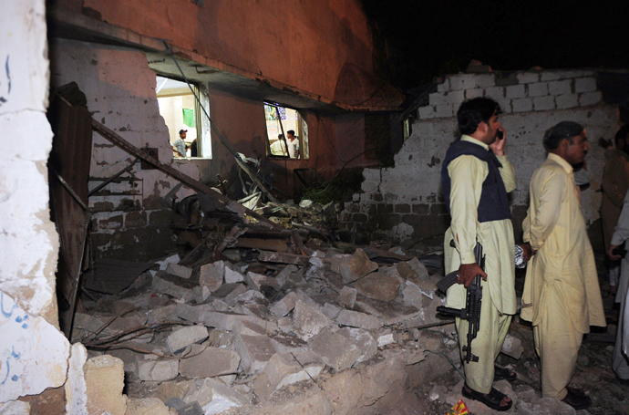 Pakistani security officials stand at the site of a bomb explosion in Karachi on April 27, 2013 (AFP Photo / Asif Hassan)