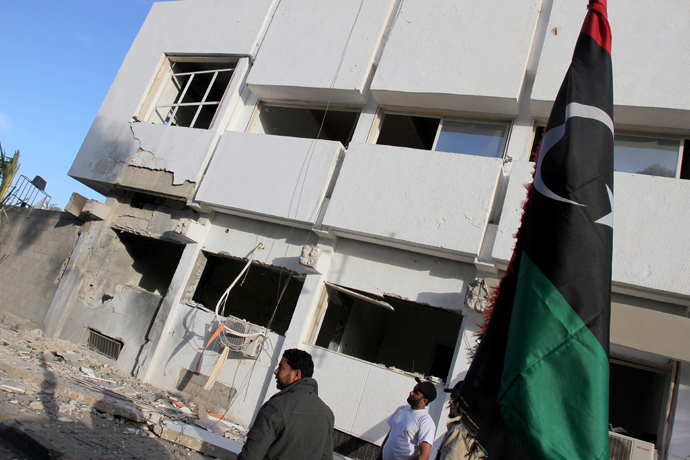 Libyan security forces and bystanders walk outside a damaged police station on April 27, 2013 in Benghazi (AFP Photo / Abdullah Doma)