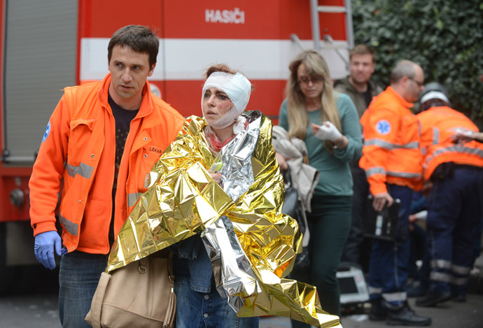 Rescue workers help a woman who was injured in a blast next to the building where an explosion happened on April 29, 2013 in Prague, Czech Republic. (AFP Photo/Michal Cizek)