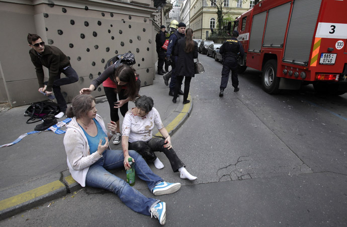 Injured people sit on a sidewalk near the area of a blast after an explosion in Prague April 29, 2013. (Reuters/David W Cerny)