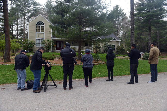 News media wait outside the home of Warren and Judith Russell, where their daughter Katherine Tsarnaeva, the widow of Tamerlan Tsarnaev, is staying, after flowers were placed there, on Coriander Lane April 23, 2013 in North Kingstown, Rhode Island. (AFP Photo / Darren Mccollester)
