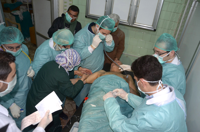 In this image made available by the Syrian News Agency on March 19, 2013, medics and other masked people attend to a man at a hospital in Khan al-Assal in the northern Aleppo province, as Syria's government accused rebel forces of using chemical weapons for the first time. The opposition denied the claim, saying instead that government forces might have used banned weapons. (AFP Photo / SANA)